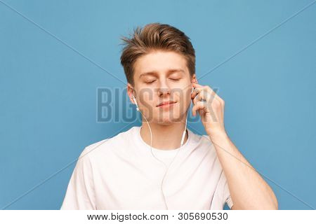 Close-up Portrait Of A Guy Listens To Music In His Headphones With His Eyes Closed And Enjoys A Blue
