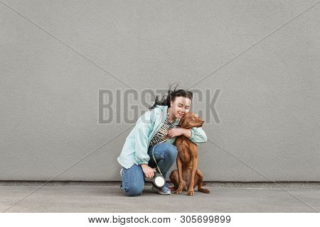Happy Owner Hugs A Beautiful Dog Against The Background Of A Gray Wall. Portrait Of A Woman With A D