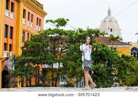 Beautiful woman on white dress walking alone at the walls surrounding the colonial city of Cartagena de Indias poster