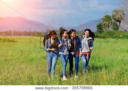 Trekking Holiday Concept.four Women Are Trekking In The Mountains With Backpack,tent,hiking Equipmen