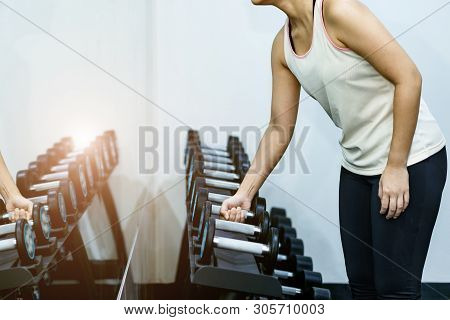 Woman Exercising At The Gym By Lifting Dumbbell.sport Equipment.concept Of Healthy