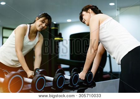 Women Exercising At The Gym By Lifting Dumbbell.sport Equipment.concept Of Healthy