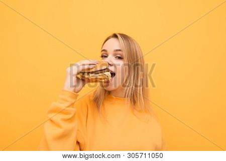 Close Up Portrait Of A Hungry Young Woman Eating Burger Isolated Over Yellow Background, Looking Int