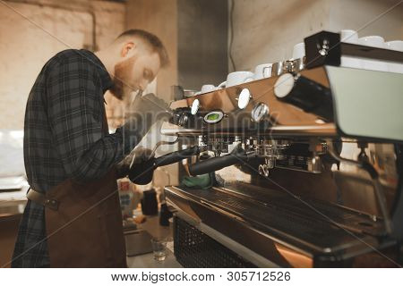 Portrait Of A Bearded Man Barista Steaming Milk On A Professional Coffee Machine. Process Of Cooking