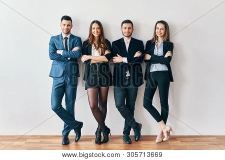 Full Length Portrait Of Young And Smiling Business People With Arms Crossed Lean To Wall In Office.