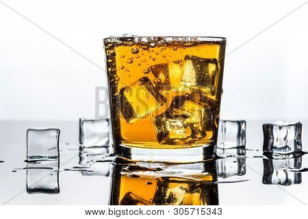 Whisky, Whiskey Or Bourbon In Glass With Ice Cubes On White Reflection Background