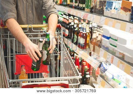 Man Holds Two Bottles Of Beer In His Hands And Puts Them In A Cart For Shopping.buyer Buys A Beer In