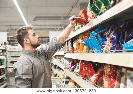 Man With A Beard Takes A Pack Of Chips From The Store Shelves. Buyer Wears A Shirt And Buys A Snack