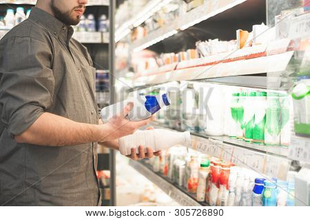 Man In A Shirt With Two Bottles Of Yogurt In His Hands. Buyer Is Buying A Dairy Product In A Superma