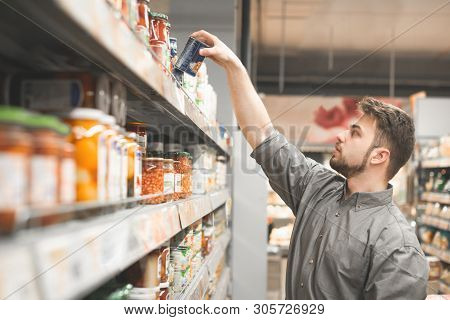 Man With A Beard Is In The Department Of Canned Vegetable Supermarket And Takes A Can From The Shelf