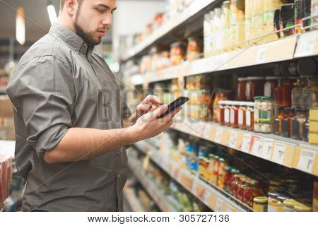 Man Is In The Department Of Canned Vegetable Supermarket And Uses A Smartphone. Buyer Looks At The S