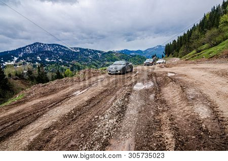Goderdzi, Georgia - May 8, 2017. Convertible Cars Going On Broken Main Dirt Road In Mountains