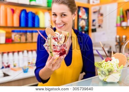 Woman in ice cream parlor presenting her newest sundae creation, looking into the camera