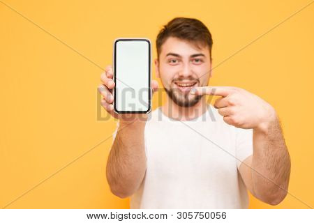 Smiling Man Holds A Smartphone In His Hands, And Shows His Finger On A White Screen On A Yellow Back