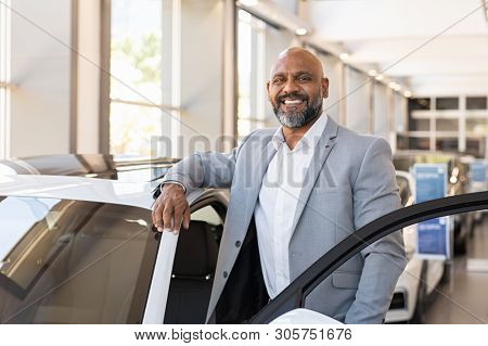 African salesman standing in car showroom near opened door of luxury car. Happy businessman buying his new suv in car salon. Smiling mature man choosing his new car.