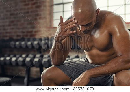 Exhausted shirtless man sitting on bench at gym. Sweaty muscular guy resting after fitness training session with copy space. Tired athlete take a break after intensive workout.