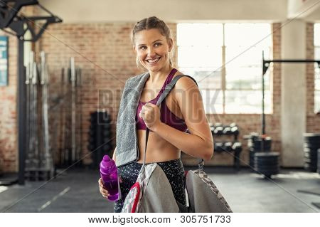 Young smiling woman in sportswear carrying gym bag. Happy fitness girl with sports bag after exercise. Portrait of energetic beautiful woman looking away ready for new inscription at the gym.