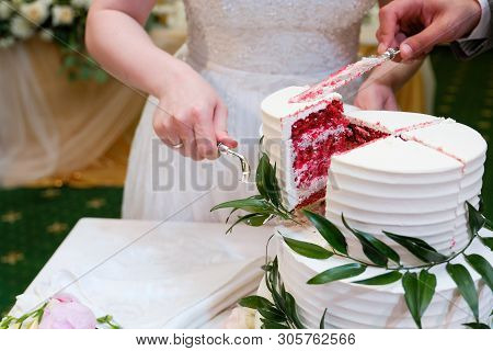 The bride and groom cut an elegant three-tiered white wedding cake decorated with natural flowers or roses and green leaves on a white wooden table. poster