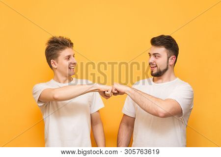 Portrait Of A Two Happy Young Men Giving Fist Bump Isolated Over Yellow Background. Two Happy Men In