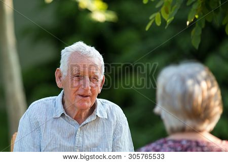 Senior Couple Sitting In Garden And Talking In Summer Time