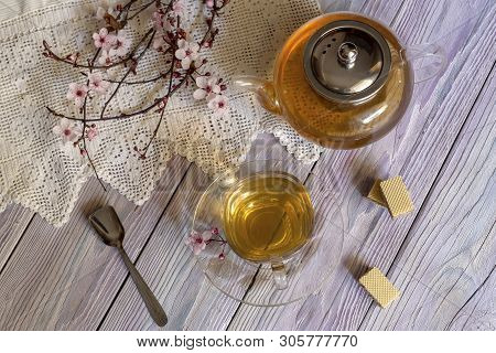 Tea Pot, Flowering Spring Branches, A Cup Of Tea And Waffles On A Wooden Table Close-up