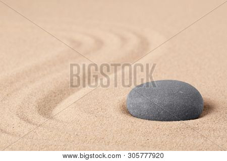 Japanese zen meditation garden with a round stone on sandy background with copy space. Concept for concentration focus and balance in life.