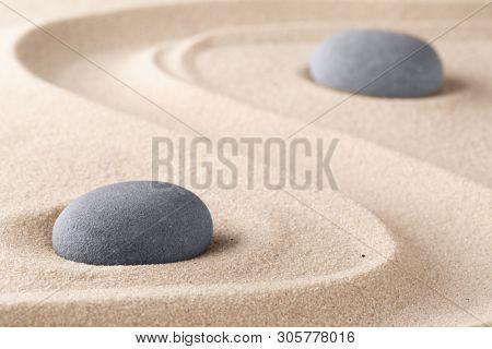 Zen garden meditation stone. Round rock on sandy texture background. Yoga or mindfulness concept.