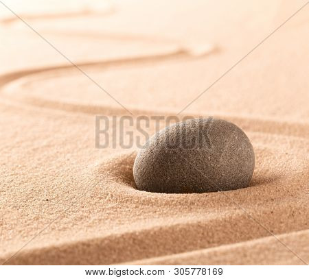 Spa wellness or mindfulness stone and sand garden. Concentration or focus point for spiritual balance and purity of mind and soul. Sandy background with copy space.