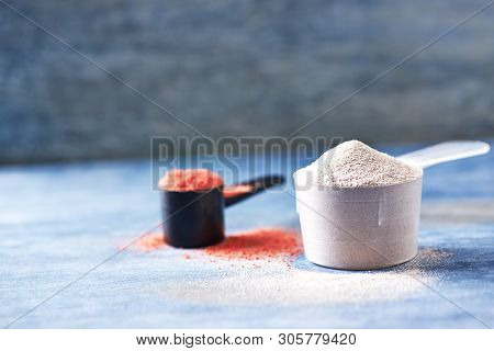 Scoop Of Whey Protein And Creatine Powder. Sport Nutrition. Rustic Wooden Background. Close Up. Copy
