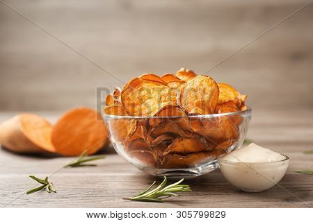 Delicious Sweet Potato Chips In Bowl, Rosemary And Sauce On Table