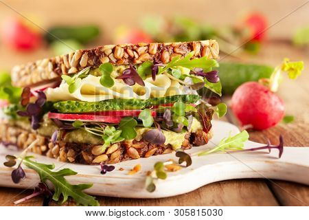 Fresh vegetarian  sandwich  with creamy avocado, cheese and fresh veggies the wooden board. Concept healthy eating. Vegetarian sandwich.