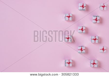 Pattern With Small Christmas Gifts Wrapped In Paper On Pink Background.holiday Greeting Card With Co