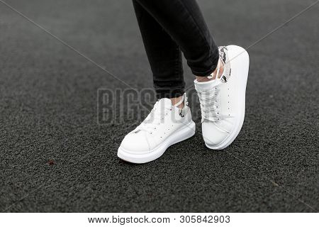 Female Legs In Stylish Black Jeans In White Leather Sneakers With Snake Pattern On The Asphalt In Th