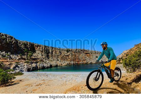 Mountain biker riding on e- bike. Man cycling MTB enduro flow trail track. Outdoor sport activity. Motion Blur picture.