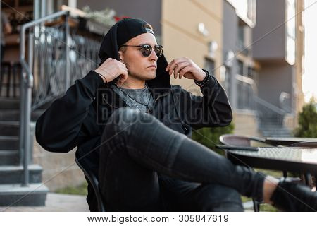Nice Urban Young Hipster Man In Black Hoodie In Stylish Sunglasses In Vintage Jeans In A Black Cap R