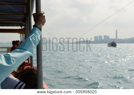 Ferry Boat To Koh Larn Island. Passenger Holds On To The Handrail On The Ship. Cityscape Of Pattaya