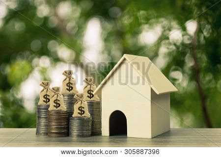 Property Investment And Home Financial Mortgage Concept. A Money Bag On Stacked Coins And House Mode