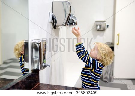 Little Caucasian Boy Drying His Hands In A Restroom. Hygiene For Child.