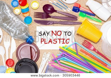 Disposable single use plastic objects such as bottles, cups, forks, spoons and drinking straws that cause pollution of the environment, especially oceans. Top view on sand