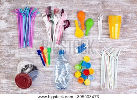 Disposable single use plastic objects such as bottles, cups, forks, spoons and drinking straws that cause pollution of the environment, especially oceans. Top view.
