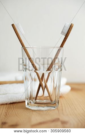 Two Bamboo Toothbrushes In A Glass With A White Towel