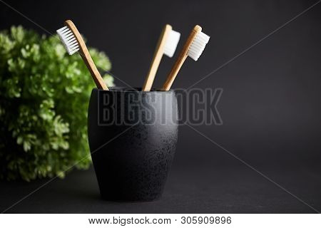 Three Bamboo Toothbrushes In A Black Glass With Copy Space