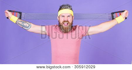 Athlete Stretching With Expander. Man Bearded Athlete Exercising With Expander Equipment. Try Stretc