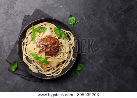 Spaghetti bolognese pasta with tomato and minced meat sauce, parmesan cheese and fresh basil. Top view with copy space