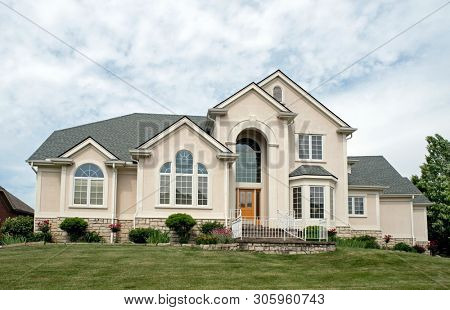 Wealthy Tan Stucco Home with Arched Entryway poster