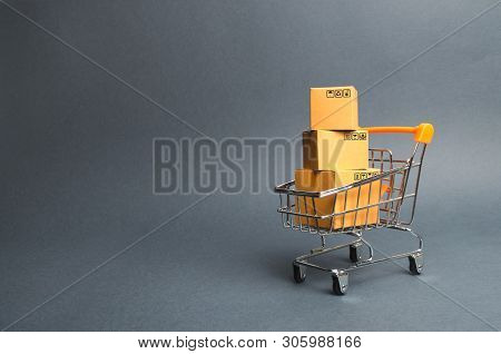 A Pile Of Cardboard Boxes In A Supermarket Trolley. Concept Of Shopping In The Online Store . E-comm
