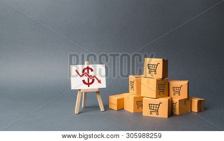 A Pile Of Cardboard Boxes And Stand With A Red Down Arrow. Decline In The Production Of Goods And Pr