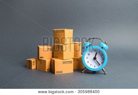 A Stack Of Cardboard Boxes And A Blue Alarm Clock. Express Delivery Concept. Temporary Storage, Limi