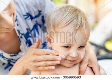 Mother Applying Sunscreen Protection Creme On Cute Little Toddler Boy Face. Mom Using Sunblocking Lo