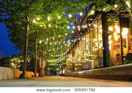 Bucharest, Romania - May 9, 2019: Decorated And Illuminated Sidewalk With A Line Of Trees, At Blue H